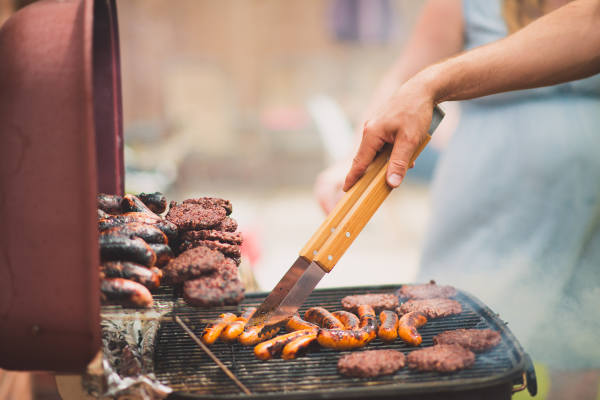 Man Cooking Burgers And Sausages On BBQ